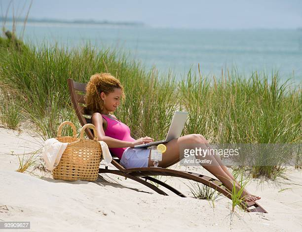 mixed race woman using laptop on beach - solo una donna giovane foto e immagini stock