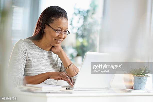 Mixed race woman using laptop