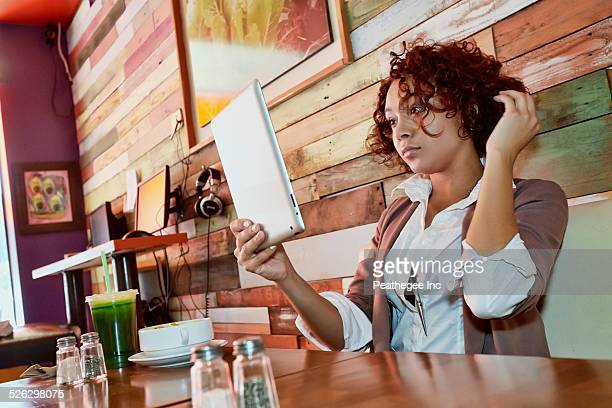 Mixed race woman using tablet computer in cafe