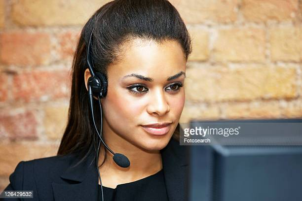 Mixed race woman using telephone headset.