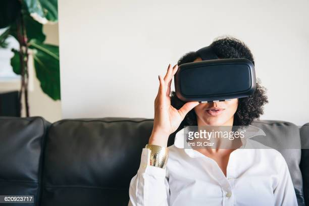 Mixed race woman using virtual reality goggles