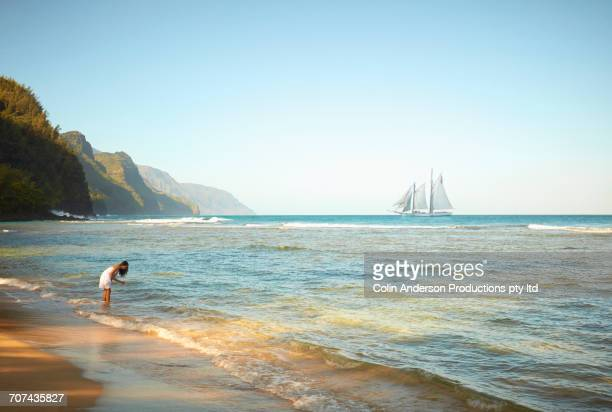 mixed race woman wading in ocean waves - seascape stock pictures, royalty-free photos & images