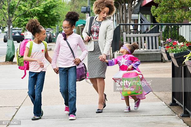 mixed race woman walking daughters to school in city - busy sidewalk stock pictures, royalty-free photos & images