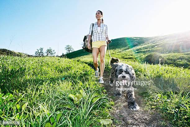 mixed race woman walking dog on grassy hillside - alleen één mid volwassen vrouw stockfoto's en -beelden