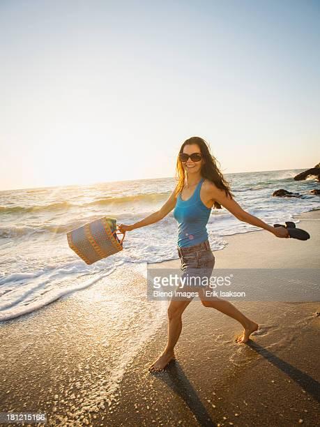 Mixed race woman walking on beach