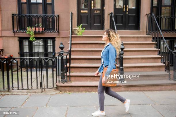 Mixed Race woman walking on city sidewalk