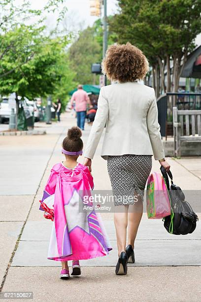 Mixed Race woman walking superhero daughter to school in city