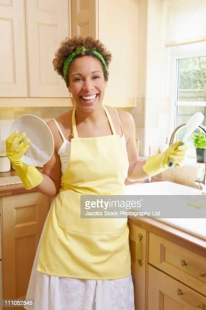 mixed race woman washing dishes - spalding england stock photos and pictures