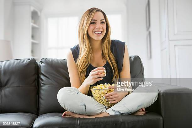 Mixed race woman watching television on sofa