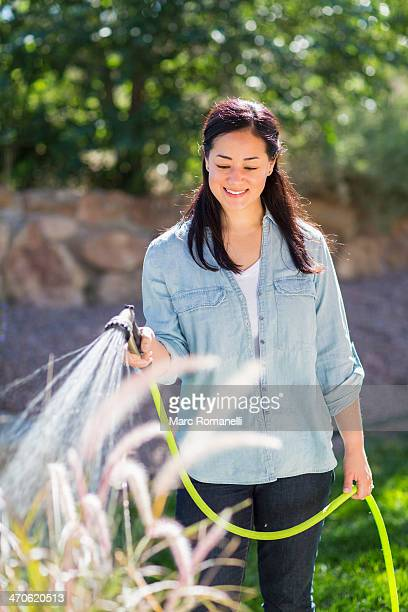 Mixed race woman watering plants in garden