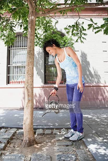 mixed race woman watering tree on urban sidewalk - person gemischter abstammung stock-fotos und bilder