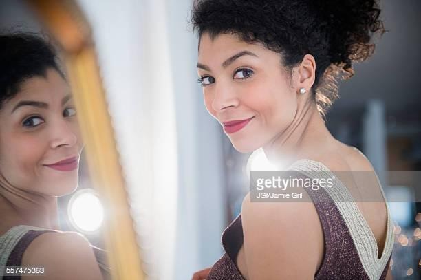 Mixed race woman wearing evening gown near mirror