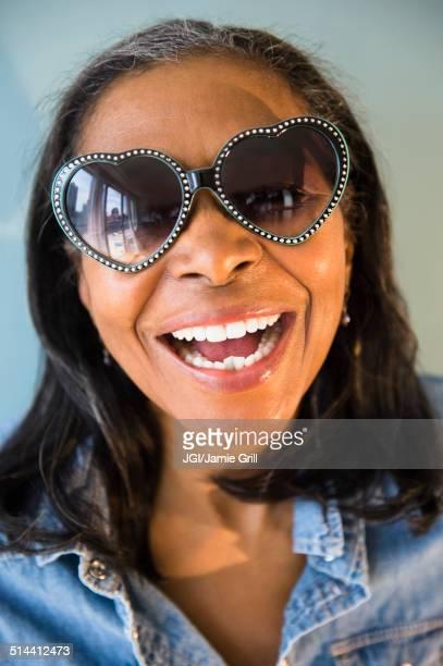 Mixed race woman wearing heart-shaped sunglasses