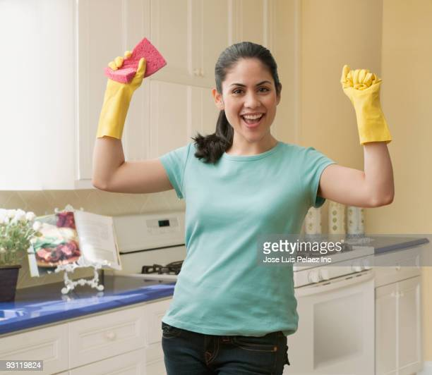 Mixed race woman wearing rubber gloves and holding sponge