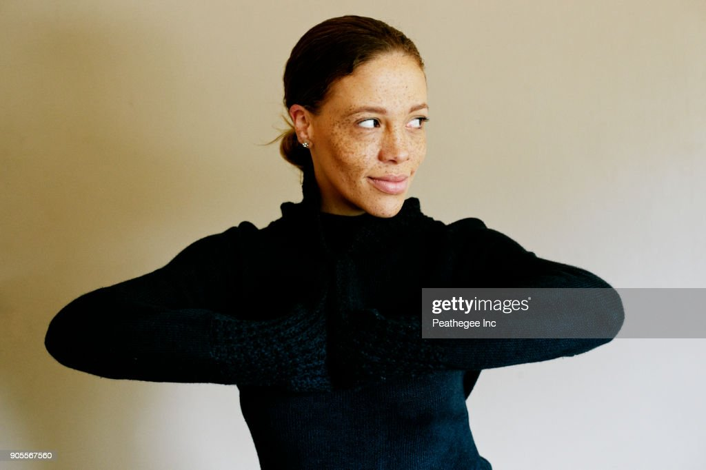 Mixed race woman wearing sweater looking away : Stock Photo