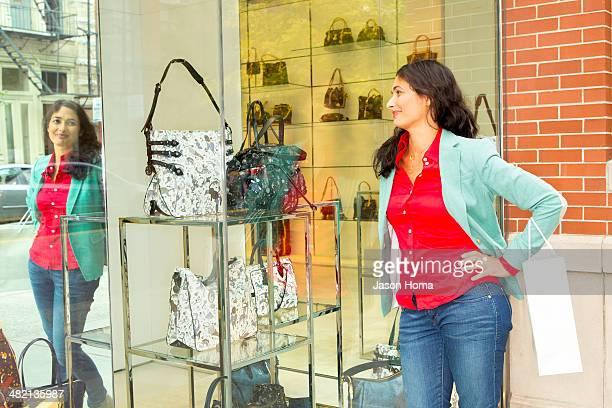 Mixed race woman window shopping at purse shop