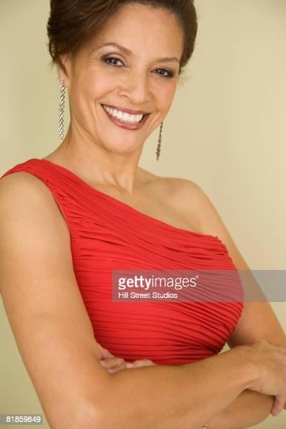 mixed race woman with arms crossed - avondjurk stockfoto's en -beelden