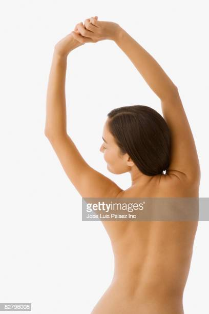 Mixed race woman with bare chest stretching
