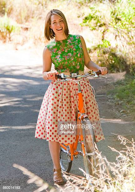 Mixed race woman with bicycle on paved path