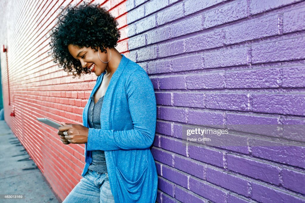 Mixed race woman with cell phone standing by colorful wall : Stock Photo