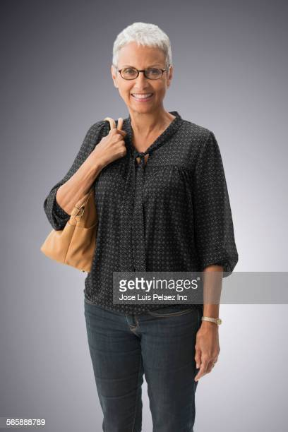 mixed race woman with eyeglasses carrying purse - grey purse stock pictures, royalty-free photos & images