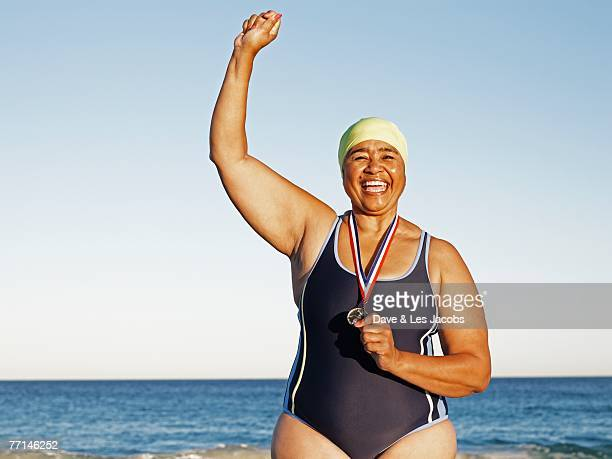 mixed race woman with medal on beach - medalist stock pictures, royalty-free photos & images