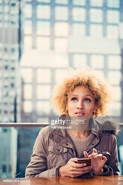 Mixed race woman with mobile phone on a roof top.