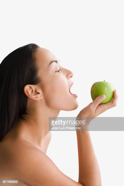 Mixed race woman with mouth open holding apple
