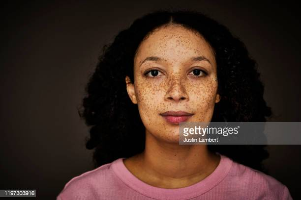 mixed race woman with pronounced freckles looking to camera - portrait stock pictures, royalty-free photos & images