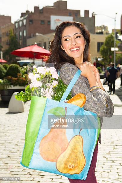 Mixed race woman with shopping bag on city street