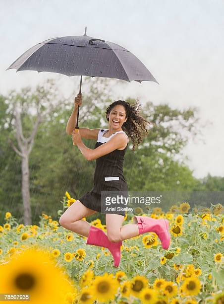 mixed race woman with umbrella jumping - レインブーツ ストックフォトと画像