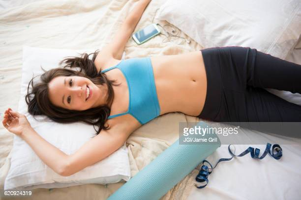 Mixed race woman with workout gear on bed