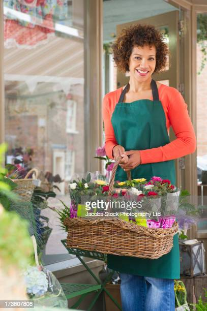 mixed race woman working in florist shop - spalding england stock photos and pictures
