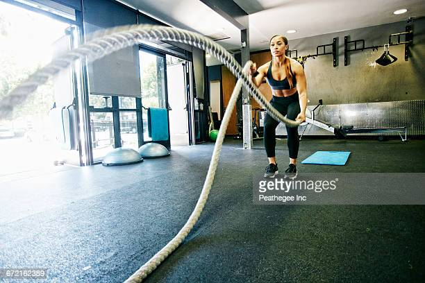 mixed race woman working out with heavy ropes in gymnasium - donna creola foto e immagini stock