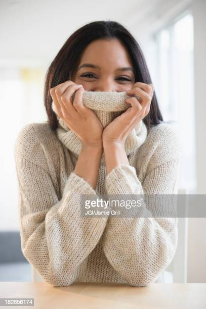Mixed race woman wrapped in sweater