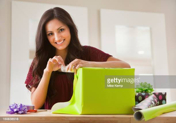 mixed race woman wrapping gift - donna bendata foto e immagini stock