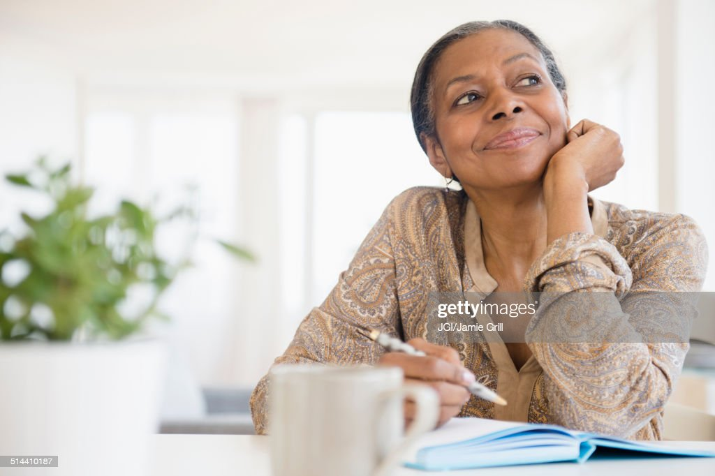 Mixed race woman writing at desk : Stock Photo