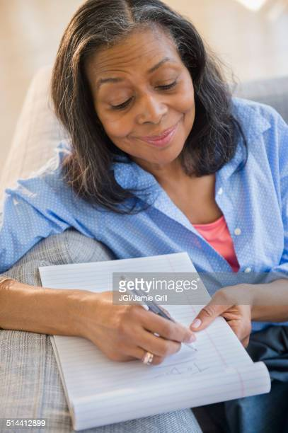 Mixed race woman writing notes on sofa