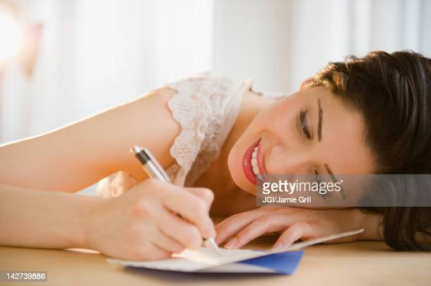 Mixed race woman writing on birthday card