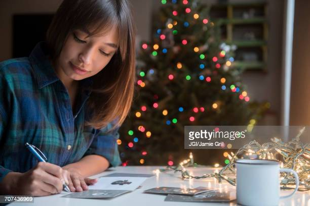 Mixed Race woman writing on card near Christmas tree