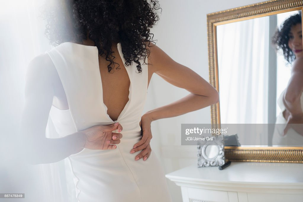 Mixed race woman zipping dress in mirror : Stock Photo