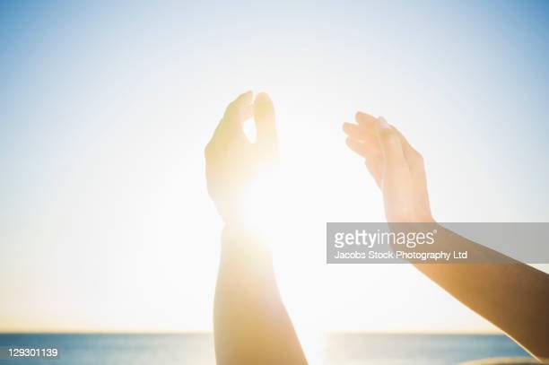 mixed race woman's hands holding the sun - gegenlicht stock-fotos und bilder