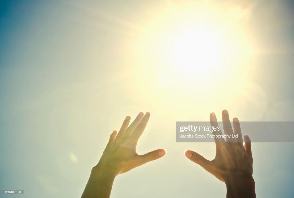 Mixed race woman's hands reaching toward sun : Stock Photo