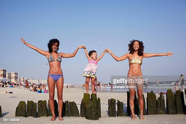 Mixed race women and girl holding hands at beach