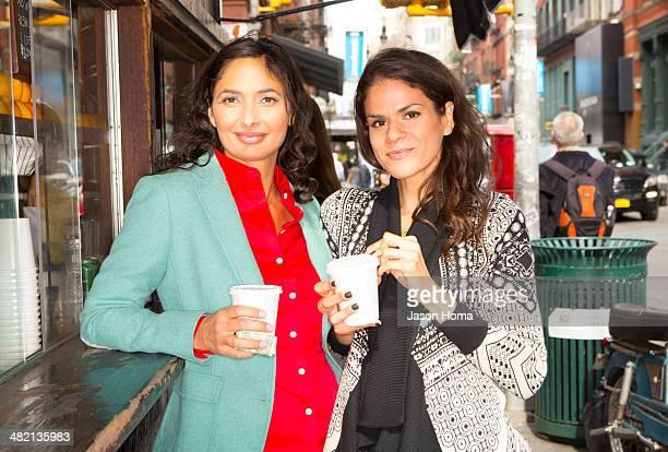 Mixed race women drinking coffee at urban food cart