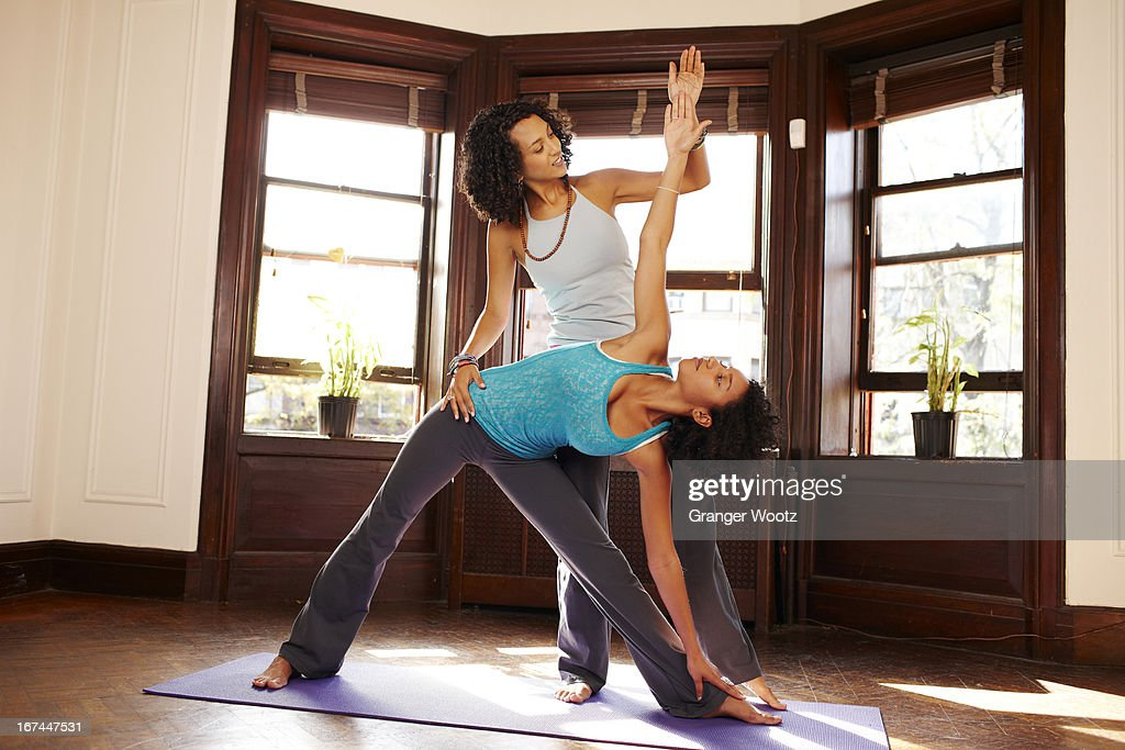 Mixed race women practicing yoga in living room : Stock Photo
