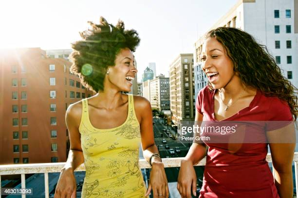 Mixed race women smiling on urban rooftop