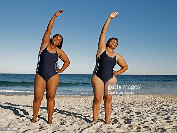 mixed race women stretching at beach - images of fat black women stock photos and pictures