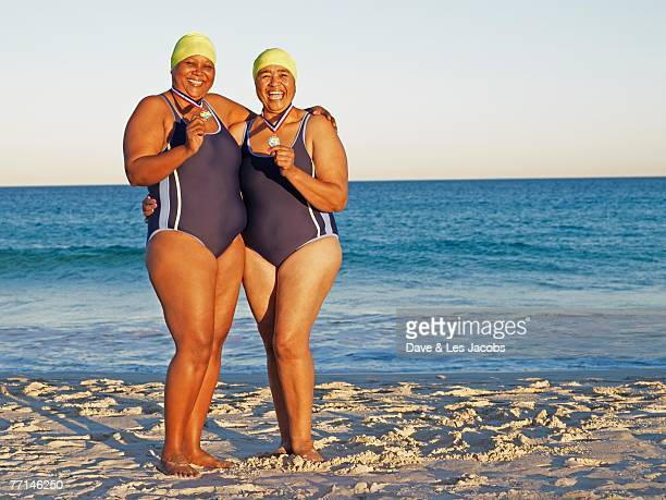 mixed race women with medals on beach - fat woman at beach stock photos and pictures