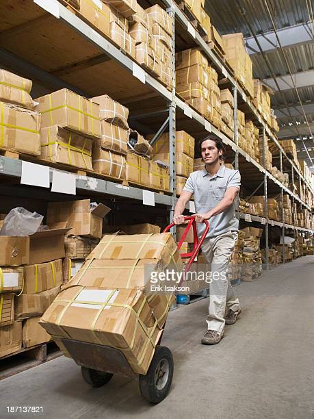 Mixed race worker carting boxes in textile factory